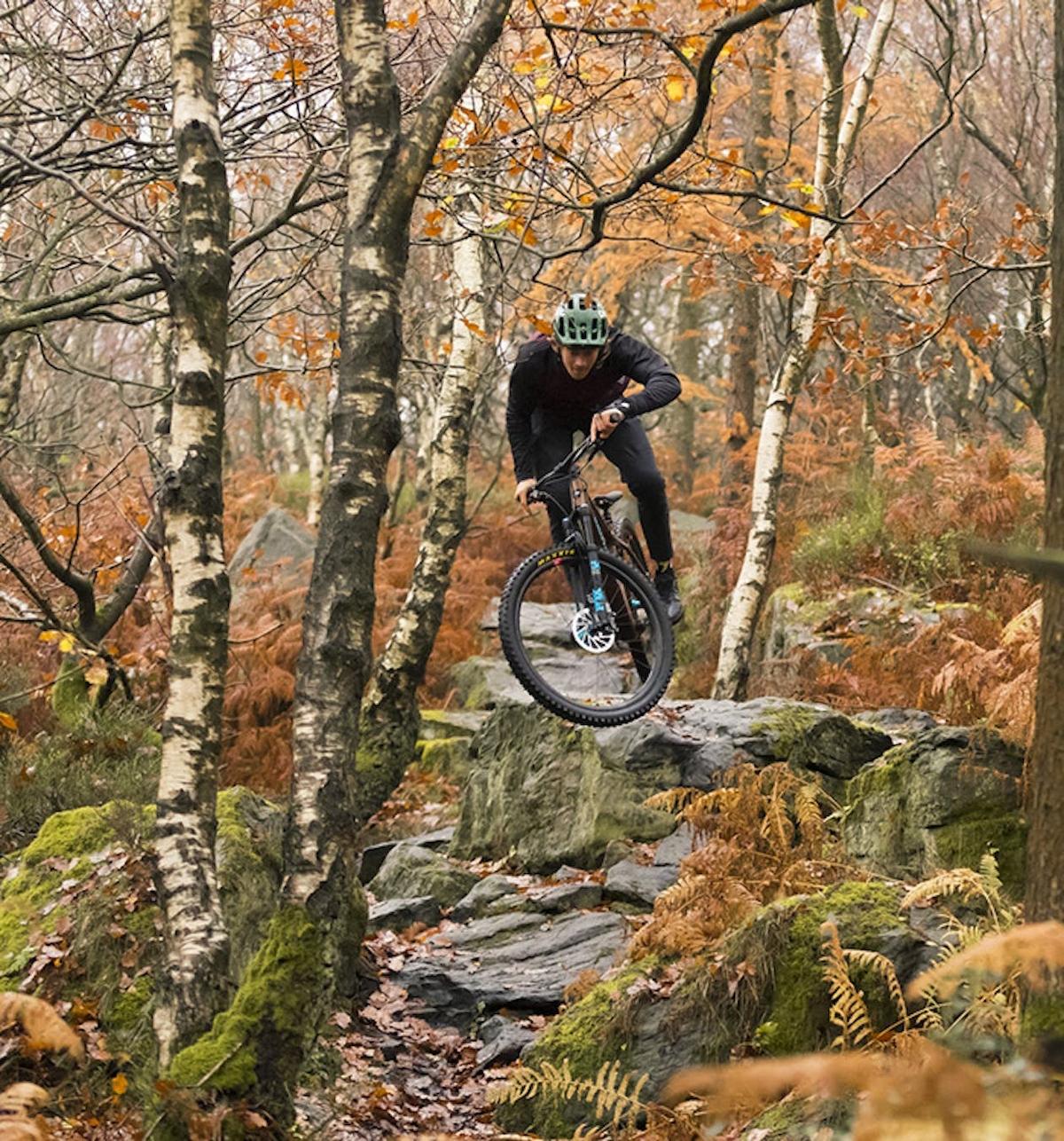 Craig Evans et son hardtail Chameleon sur un rocher et dans un chemin couvert de feuilles