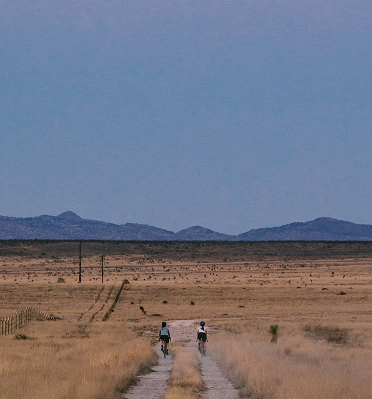Two cyclists riding Juliana Quincy's down a dirt road with mountains in the background