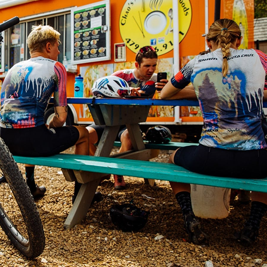 Santa Cruz htSQD XC Team sitting next to an orange food truck