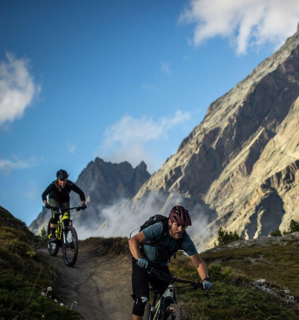 2 mountain bikers riding Santa Cruz Hecklers with a mountain backdrop