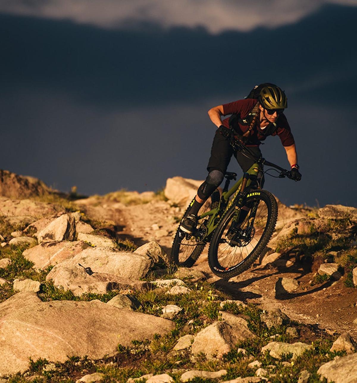 Riding the Juliana Maverick down a singletrack trail surrounded by rocks
