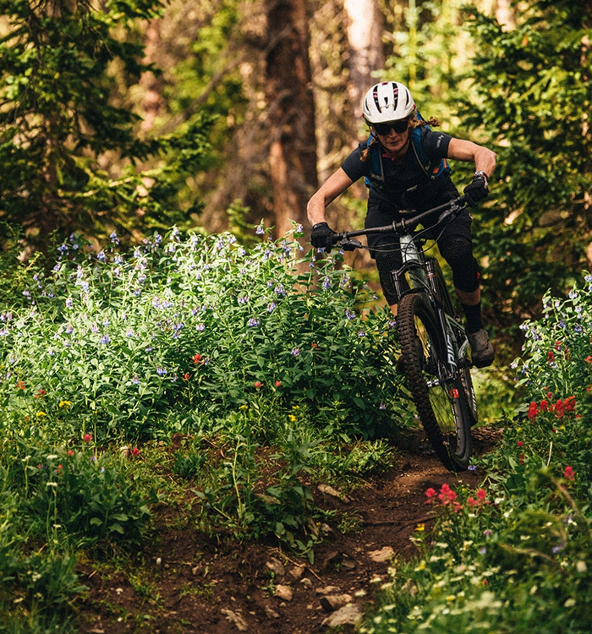 Riding the Juliana Joplin on a dirt trail surrounded by flower bushes